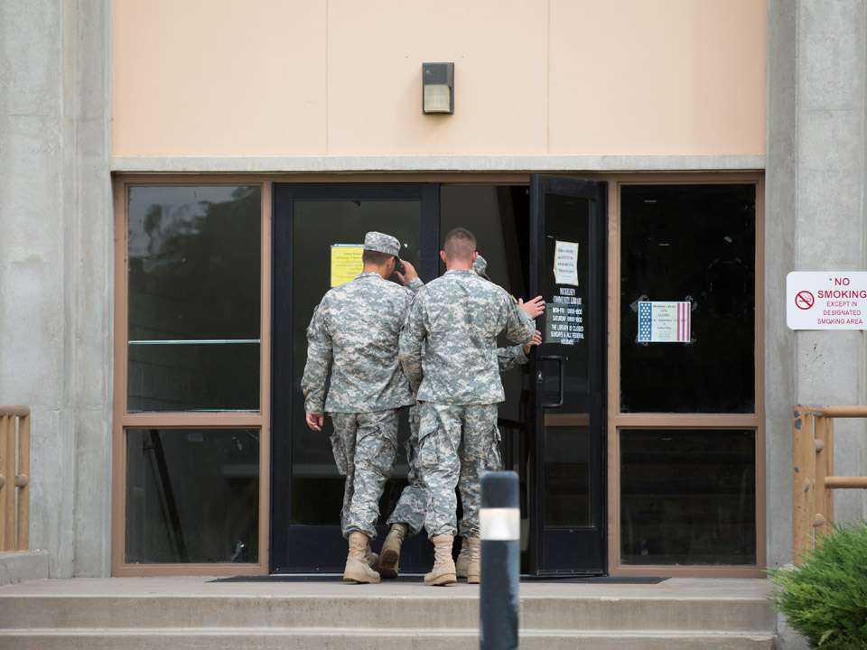 two soldiers walking into building