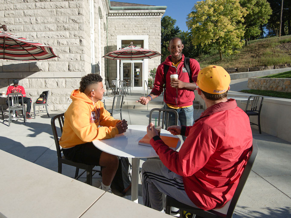 students talking outside at table