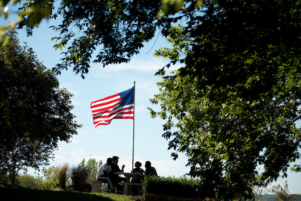 students sitting by American flag
