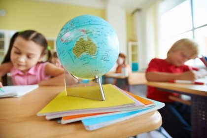 globe on desk with school children