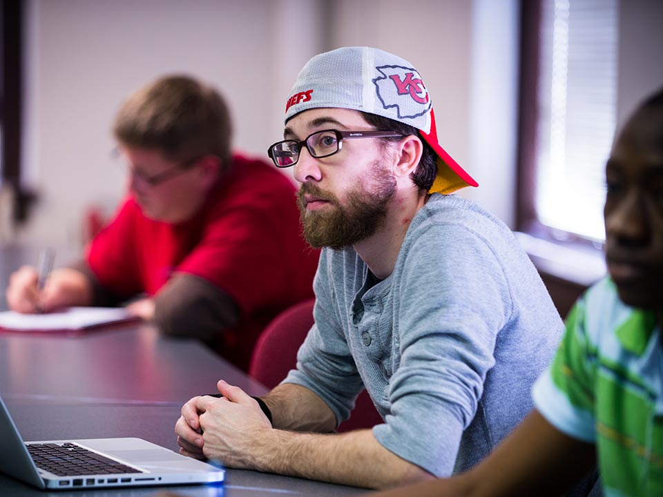 student in hat in class