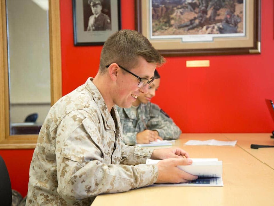 student at desk in military uniform